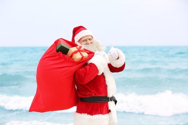 바다 표면에 선물로 가득한 큰 빨간 가방을 가진 정통 산타 클로스