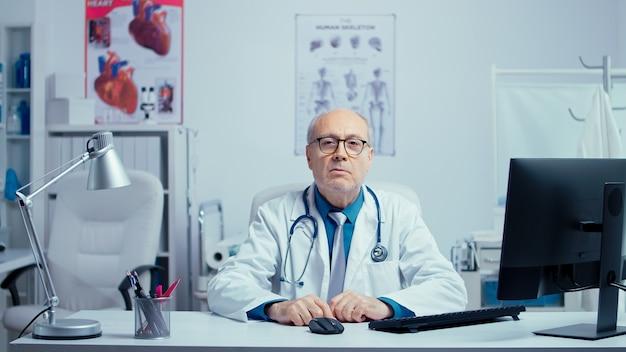ズームコールを介してオンライン相談を行う本物の先輩医師。現代のテクノロジーとインターネットヘルスケア。技術とウェブを使用して患者と話している古い経験豊富な開業医