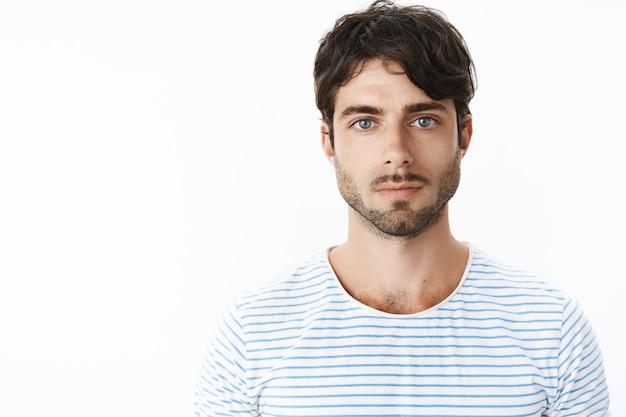 Подлинный снимок молодого привлекательного парня с легкой сыпью на шее после бритья, который выглядит строго и серьезно спереди, без эмоций, холодных и уверенных, смотрит вперед темно-синими глазами.