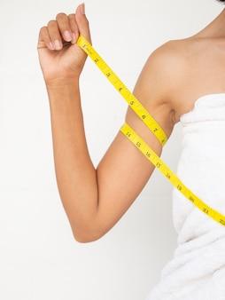 흰색 바탕에 흰색 수건으로 손을 측정하는 정통 피부 황갈색과 날씬한 여성. 날씬하고 좋은 건강 관리 개념을 위해 다이어트를 하십시오.