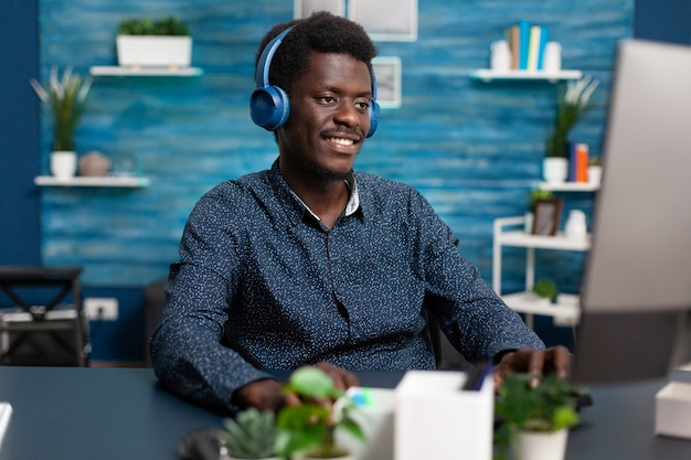 Authentic smiling african american man using laptop and headphones to work from home and learn freel...