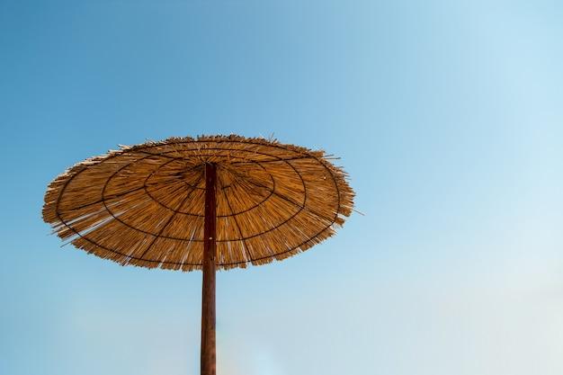 Аутентичный зонт от солнца на пляже, против голубого неба.