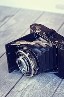 木製のテーブルの上の本物のビンテージ写真カメラ