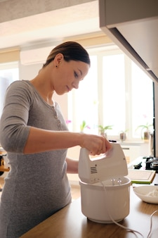 Authentic woman using a handheld mixer