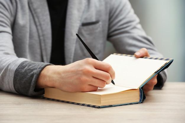 木製のテーブルで自分の本のサインに署名する著者
