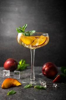 Авторский коктейль с фруктовым нектарином в высоком бокале мартини сдержанный