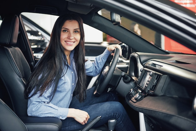 Auto business, car sale, consumerism and people concept - happy woman taking car from dealer in auto show or salon