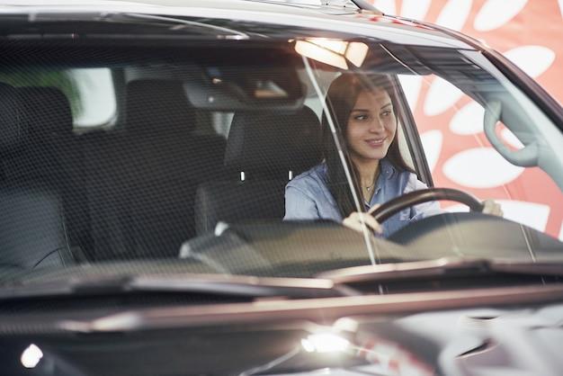 Affari automobilistici, vendita di automobili, consumismo e concetto della gente - donna felice che prende chiave dell'automobile dal commerciante nell'esposizione automatica o nel salone