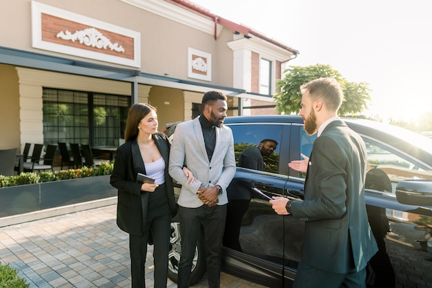 Auto business, car sale, technology and people concept - business couple, african man and caucasian woman with car dealer man standing near the black car in the yard of auto salon outdoors