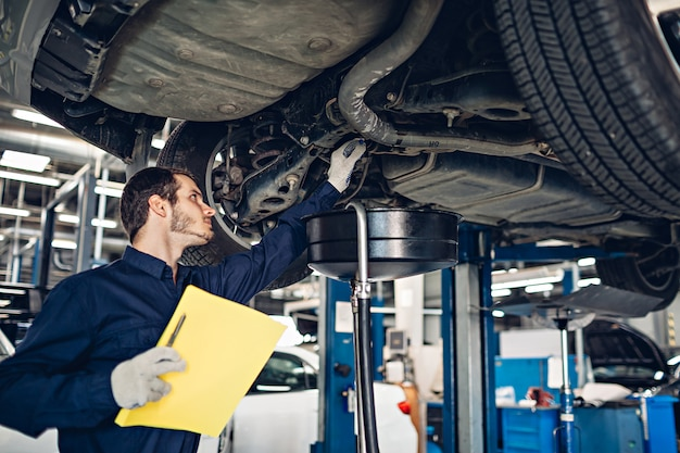 Auto car repair service center. mechanic examining car