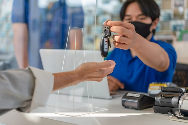 Человек обслуживающего персонала авто дает ключ от машины владельцу автомобиля после обслуживания в гараже