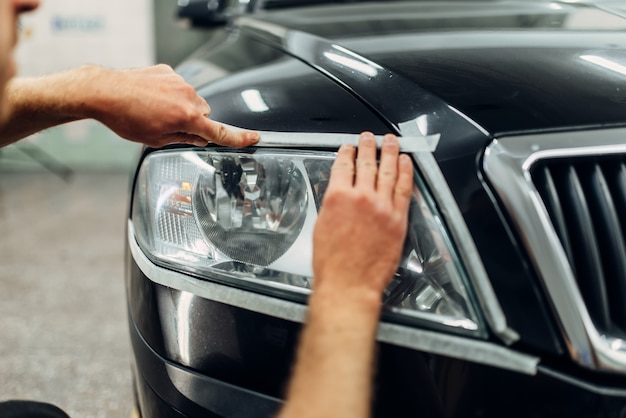 洗車サービスでの車のヘッドライトの自動詳細。労働者は研磨用ガラスを準備します
