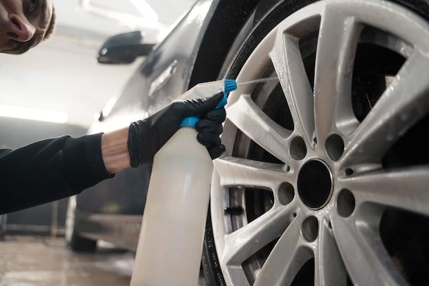 Работник автозапчастей применяет химию к колесам.