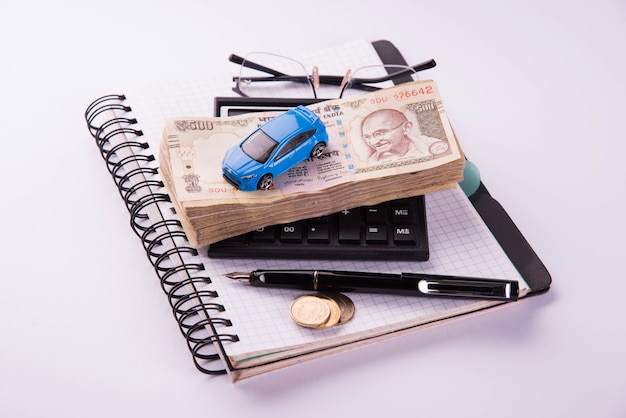 Auto finance or loan in india -  concept showing toy car model, keys, indian currency notes and calculator for emi calculations etc arranged over clear background