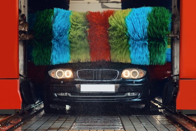 Auto in foam on automatic car wash with colorful brush, nobody. vehicle cleaning service or business, express carwash station
