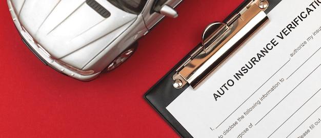 자동차 보험 양식입니다. 빨간색 배경에 클립보드와 자동차 장난감이 있는 사무실 책상. 배너 사진