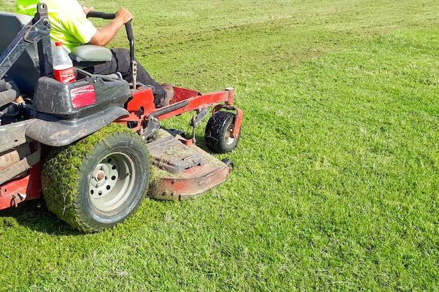 Auto lawn mower. a man rides a lawn mower. lawn care. riding mower. grass