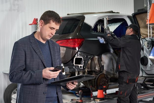 Автомеханик и техник работают в ремонтной мастерской