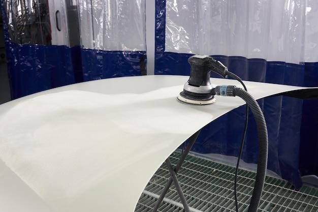 Автомеханик, полировка и полировка автомобиля в авторемонтной мастерской с орбитальной полировкой, чистка основного слоя