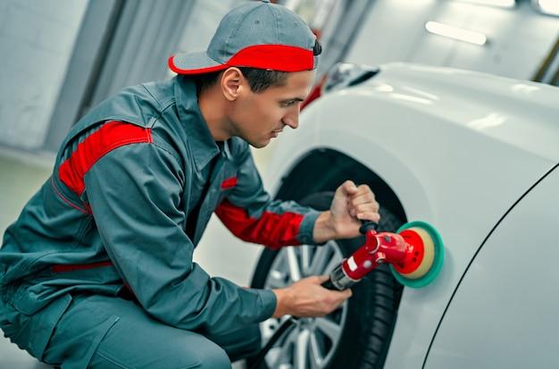 Автомеханик полирует кузов автомобиля. ремонт и обслуживание автомобилей.