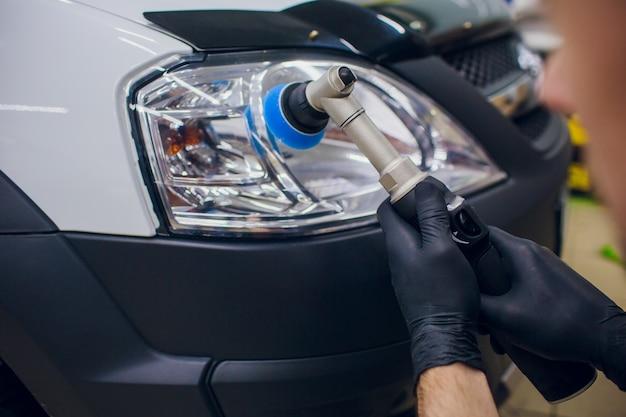 Auto mechanic buffing and polishing car headlight