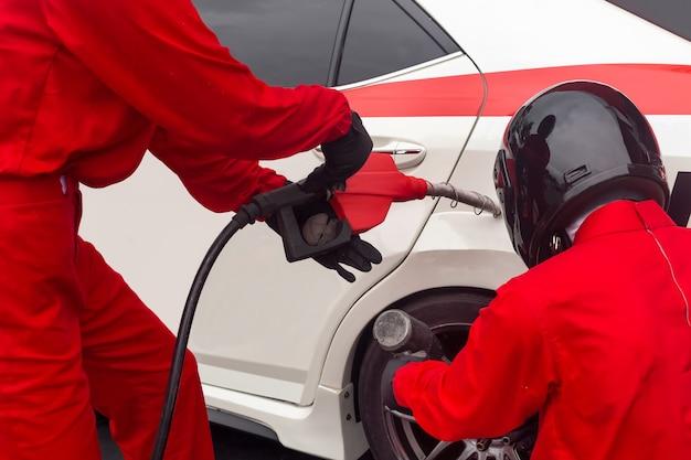 自動車整備士が車のホイールを交換して燃料を充填する