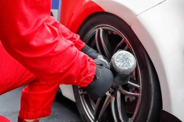 Автомеханик, меняющий колесо автомобиля