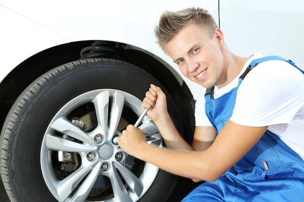 Автомеханик, меняющий колесо
