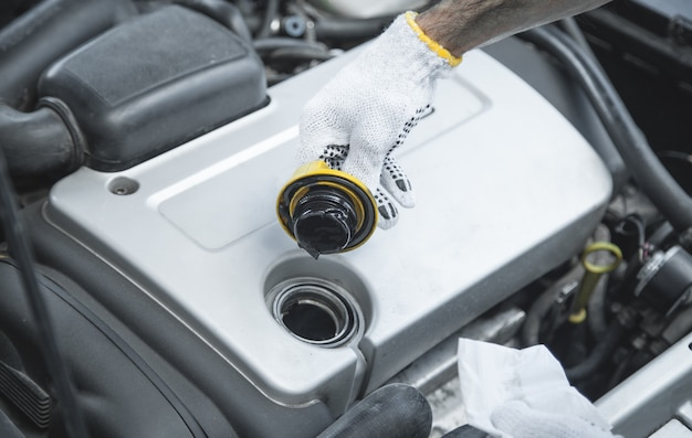 Auto mechanic check system oil of car engine.