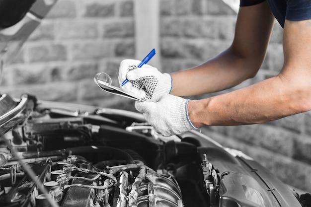 Автомеханик проверяет двигатель автомобиля в гараже.