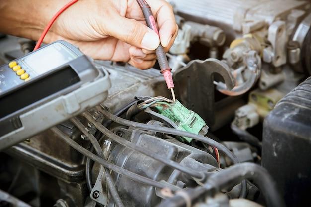 Автомеханик, проверяющий электрическую систему в двигателе автомобиля.