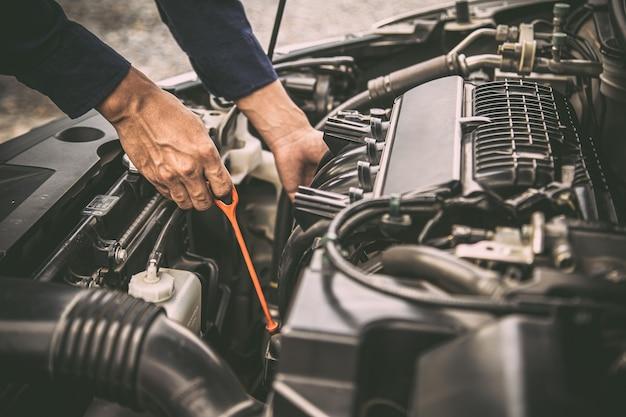 Auto mechanic checking vehicle engine oil level.