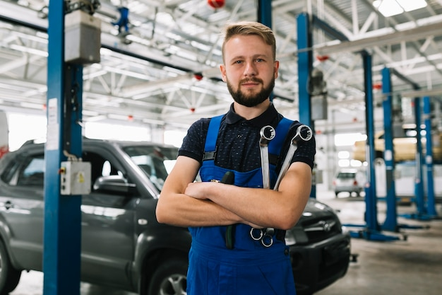Auto mechanic crossing hands with spanners