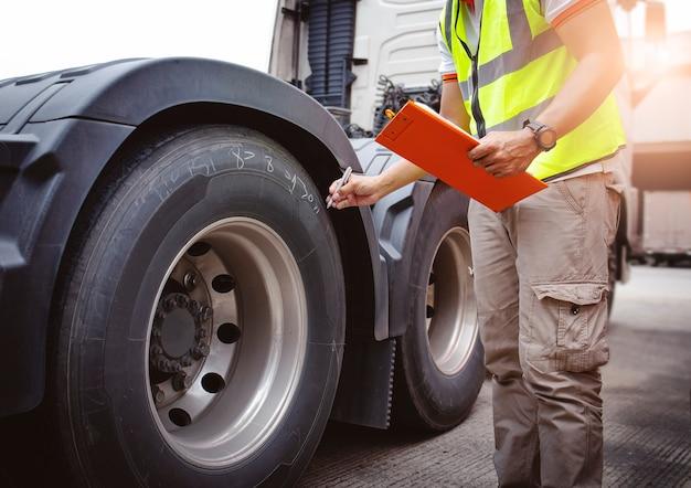 Водитель автомеханика с буфером обмена проверяет колеса и шины грузовика безопасность осмотра грузовика