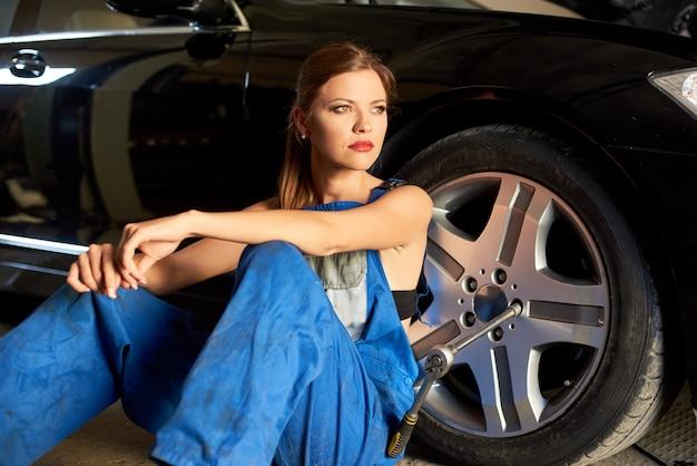 自動車整備士の女の子が黒い車のホイールの近くに座っています。