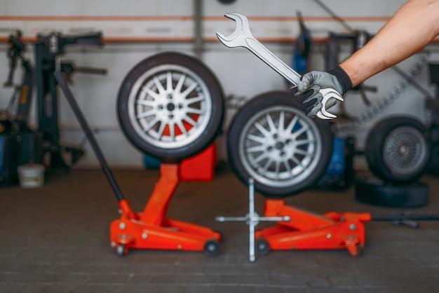 Рука автомеханика держит ключ, шиномонтаж. профессиональный осмотр автомобильных шин в мастерской, колеса на домкратах, инструменты и оборудование для ремонта