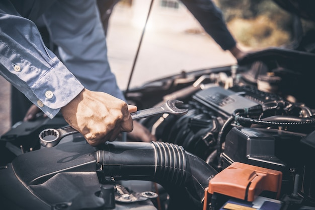 Auto mechanic hands using wrench to repair a car engine.