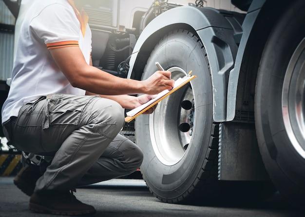クリップボードを保持している自動車整備士は、トラックの車輪とタイヤの検査安全トラックの車輪をチェックしています