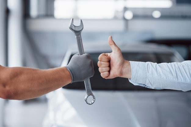 The auto mechanic holds the key in the client's hand and lifts his thumb up. well done work