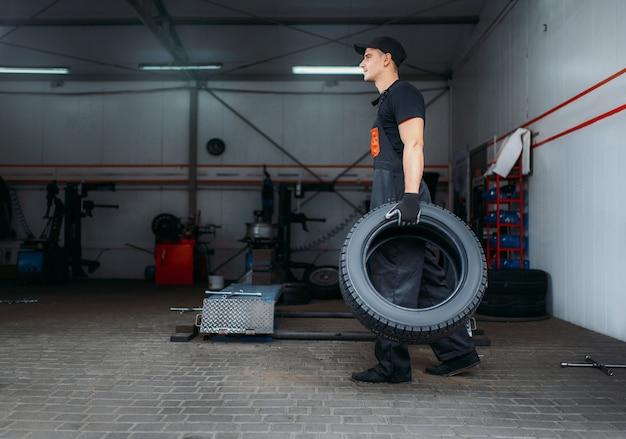 자동차 정비사는 두 개의 새 타이어를 보유하고 수리 서비스를 제공합니다. 작업자가 차고에서 자동차 타이어를 수리하고 작업장에서 전문 자동차 검사