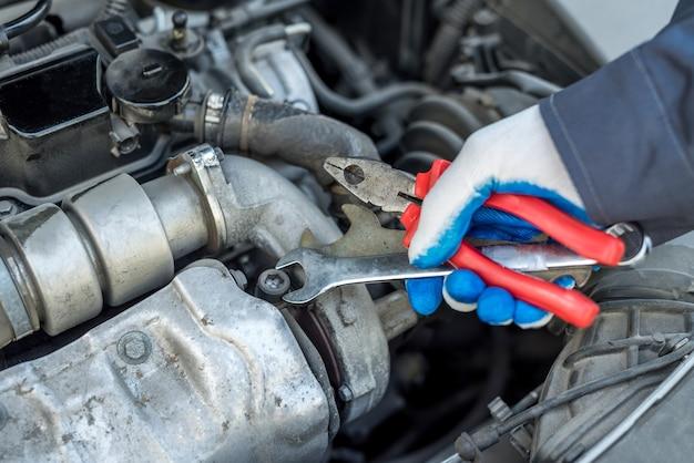 レンチキーとツールを保持している自動車修理の自動車整備士。自動車診断
