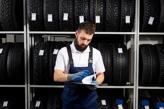 제복을 입은 자동차 정비사는 타이어의 특성을 읽고 문서를 손에 들고 서 있습니다. 백그라운드에서 구색 랙