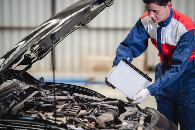 自動車整備士が、お店で電池交換サービスを利用するようになったお客様のために、新しい電池に交換しようとしています。