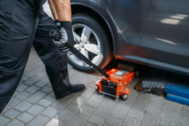 자동차 정비사는 타이어 서비스에서 차를 잭합니다. 기술자는 차고의 자동차 타이어 수리, 작업장의 전문 자동차 검사, 수리공