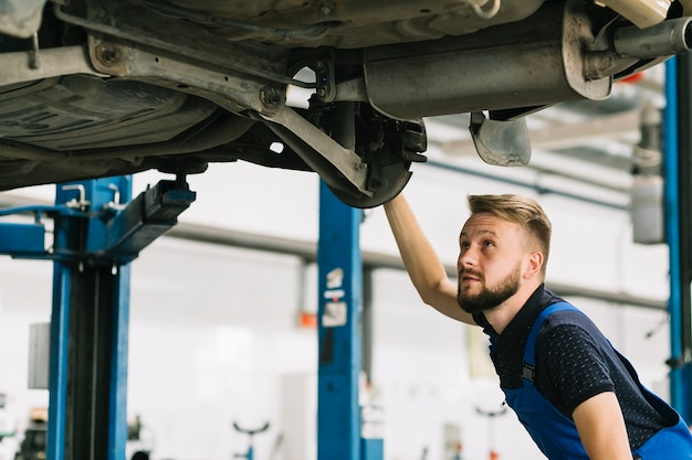 Auto mechanic looking car's bilge