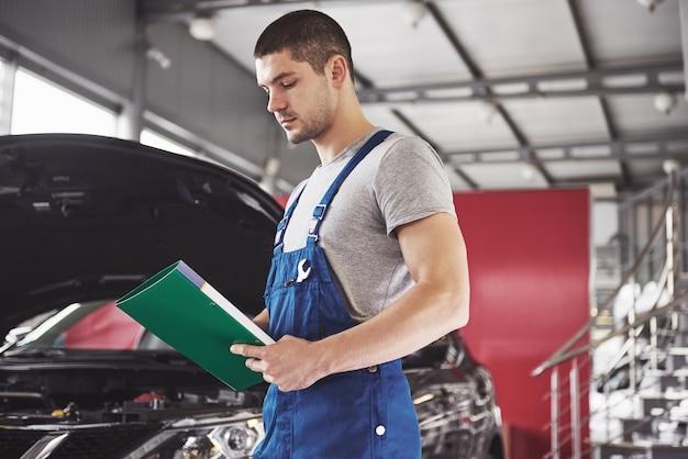 ワークショップでクリップボードを持った自動車整備士またはスミス。