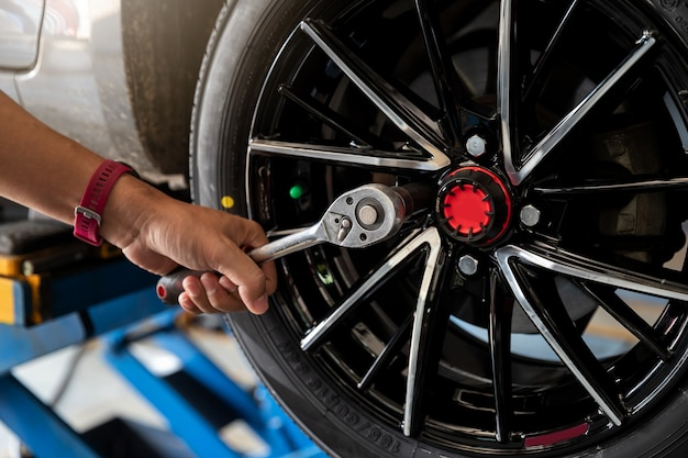 Auto mechanic man's hand changing tire in auto repair shop.
