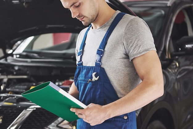 Auto mechanic man or smith with clipboard at workshop.