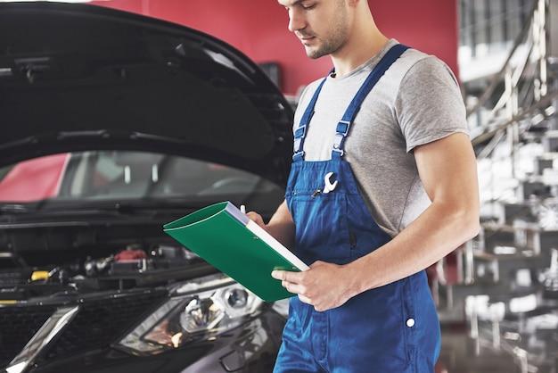 Uomo meccanico auto o fabbro con appunti in officina.