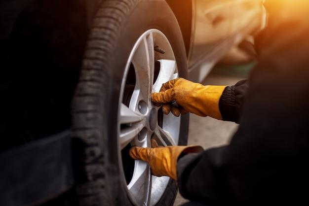 Автомеханик с электрической отверткой меняет шину снаружи. автосервис. руки заменяют шины на колесах. концепция установки шин.